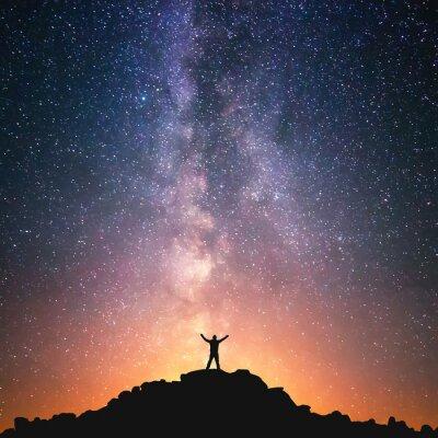 Fototapet Människan och universum. En person står på toppen av kullen bredvid Vintergatan med händerna upp i luften.