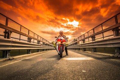 Fototapet Moto da strada Pronta alla partenza sotto un cielo rosso al tramonto