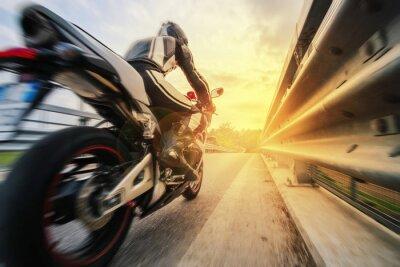 Fototapet Moto da strada sfreccia vicino al skyddsräcke al tramonto