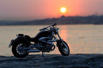 Fototapet Motorcykel på klipporna i solnedgången och gyllene timmar