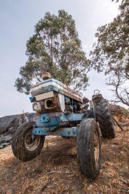 Fototapet Nära bild av en övergiven traktor på landsbygden.