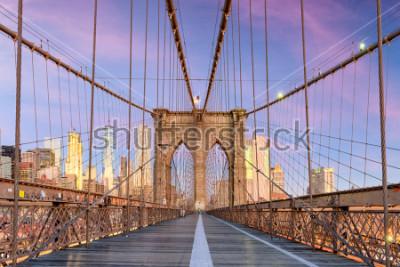 Fototapet New York, New York on the Brooklyn Bridge Promenade facing Manhattan's skyline at dawn.