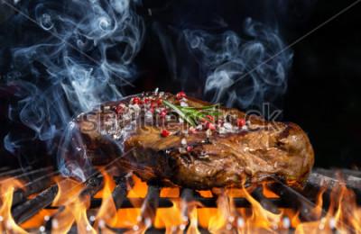 Fototapet Nötköttbiff på grill i eld med svart bakgrund