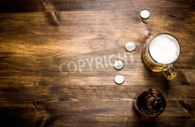Fototapet Öl stil- flaska, öl i glaset och täcker på träbord.