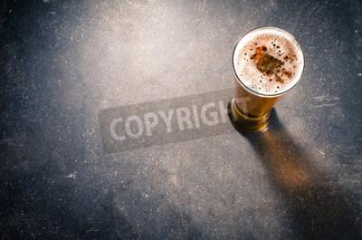 Fototapet Ölglas på mörk bord