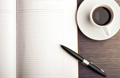 Fototapet Öppna en tom vit anteckningsblock, penna och kaffe på skrivbordet