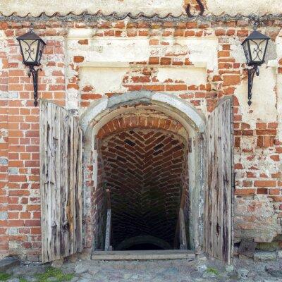 Fototapet Öppnade väderbitna trä dörrar som leder till hålan i ett gammalt slott