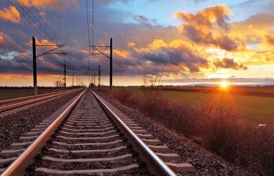 Fototapet Orange solnedgång i låga moln över järnvägen