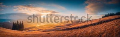 Fototapet Panorama över solnedgången i en Karpaterna med en underbar guldbelysning på en kulle