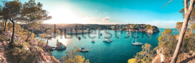 Fototapet Panoramautsikt över en strandvik med turkosblått vatten och segelbåtar och yachter vid ankaret med inramade tallar. Härliga romantiska Cala Portals Vells, Mallorca, Spanien. Balearerna