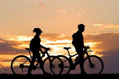 Fototapet par med cykel vid solnedgången