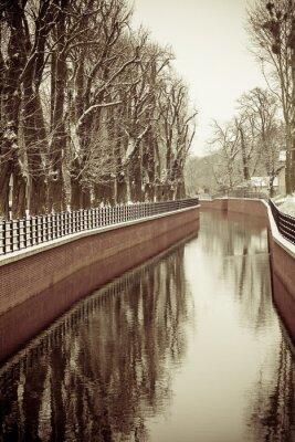 Fototapet Park med floden och bank täckt med snö