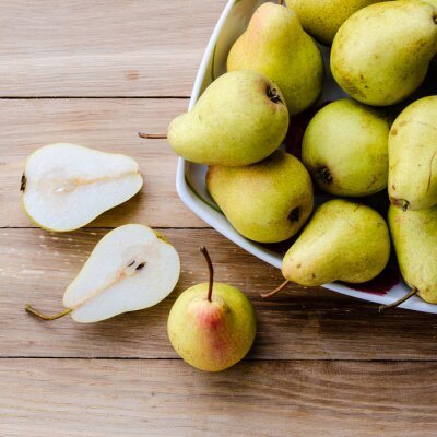 Fototapet päron i en skål och päron halvor på en trä bakgrund
