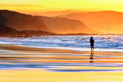 Fototapet person som kör på stranden i solnedgången