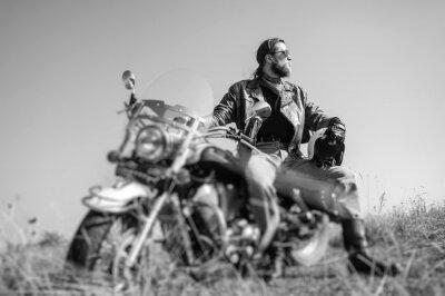 Fototapet Porträtt av en ung man med skägg som sitter på hans kryssare motorcykel och tittar mot solen. Människan bär skinnjacka och blå jeans. Låg synvinkel. Tilt linseffekt oskärpa. Svartvitt