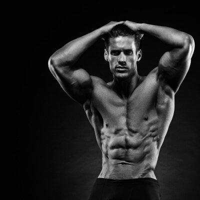 Fototapet Porträtt av en vacker muskulös kroppsbyggare poserar