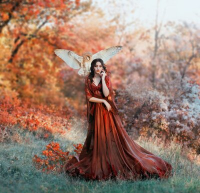Fototapet pretty young girl with black hair in cold forest, orange foliage of trees, fairy of autumn season in long red burgundy vintage dress with chic train, lady with white owl on shoulder, bloody sorceress