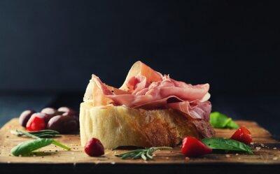 Fototapet Prosciutto med bröd på en träskiva med oliver
