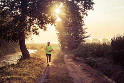 Fototapet Ragazzo che corre all'alba su strada di campagna in estate