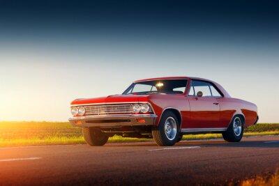 Fototapet Retro röd bil bo på asfaltvägen vid solnedgången