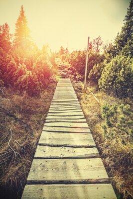 Fototapet Retro stiliserade berg trä väg i bergen vid solnedgången.
