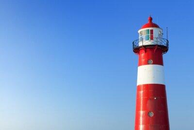 Fototapet Röd och vit fyr och en klarblå himmel