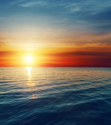 Fototapet röd solnedgång över mörka vatten