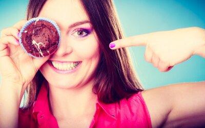 Fototapet Rolig kvinna håller kaka i handen täcker hennes ögon