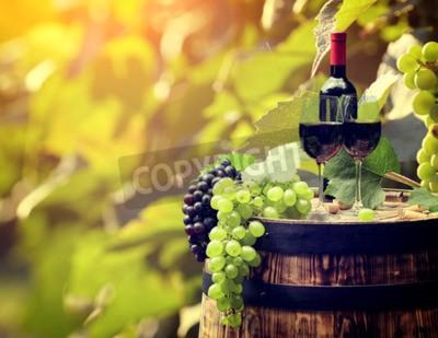 Fototapet Rött vin flaska och ett glas vin på wodden fat.