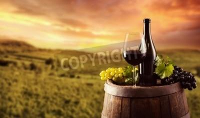 Fototapet Rött vin flaska och glas på trä fat. Vingård på bakgrund