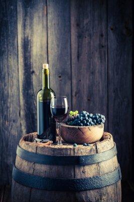 Fototapet Rött vin med färska druvor på gamla fat