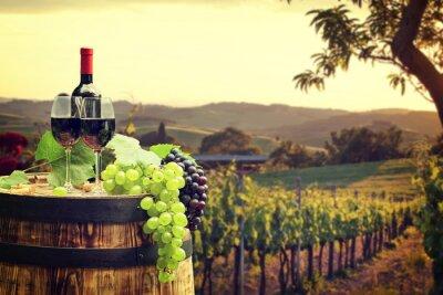 Fototapet Rött vin med fat på vingård i grönt Toscana