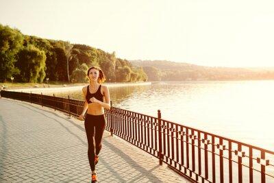 Fototapet Running kvinna. Löpare jogging i soliga ljus. kvinnlig fitnessanlä