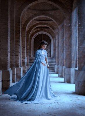 Fototapet Sad Snow Queen walks in old castle. blue silk long raincoat train flying motion. Elven hairstyle cute face. Vintage fantasy art retro style. Frozen Fabulous woman photo shoot. sun magic shine rays