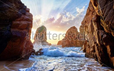 Fototapet Sandstrand bland stenar på kvällsnedgången. Ursa Beach nära Cape Roca (Cabo da Roca) vid Atlantkusten i Portugal. Sommarlandskap.
