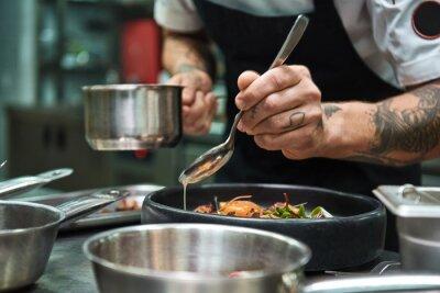 Fototapet Secret recipe. Close up photo of chef hands with several tattoos adding a sauce to italian pasta Carbonara.
