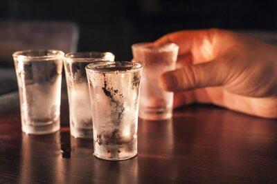 Fototapet Shot glas vodka i handen på ett träbord.