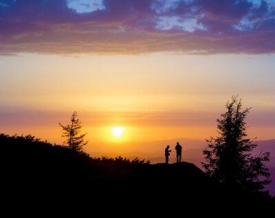 Fototapet Silhuetter av två personer som stod på en klippa nära trädet och tittar mot solen. Solnedgång i bergen. Sommar i den ukrainska Karpaterna