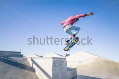 Fototapet Skateboarder gör ett trick i en skatepark