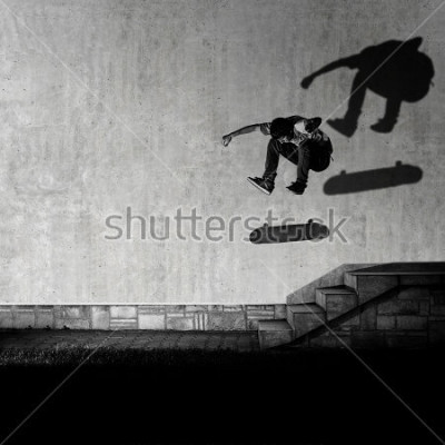Fototapet Skater making 360 flip trick from 4 stairs - artistic motion blur shot in black and white color tone.