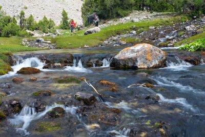Fototapet Snabb och omfattande kaskad flod Snabbt flytta vatten levande steniga stenar och grupp människor som gick på grön äng bakgrund