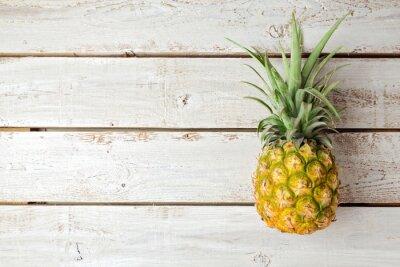 Fototapet Sommar bakgrund med ananas på träskiva