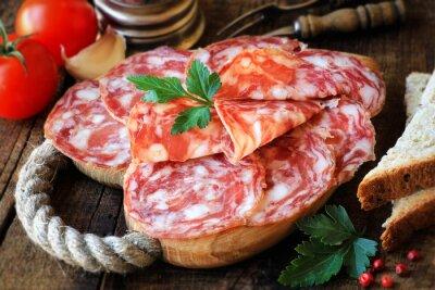Fototapet Spanska tapas - skivad salami på rustikt trä skärbräda med bröd och tomater