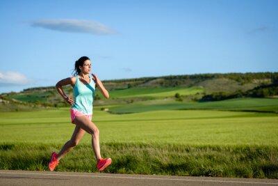 Fototapet Sportig kvinna som kör fort på landet väg. Kvinnliga idrottare utbildning utomhus.