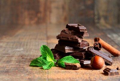 Fototapet Stack av choklad skivor med myntablad, hasselnöt och kanel.