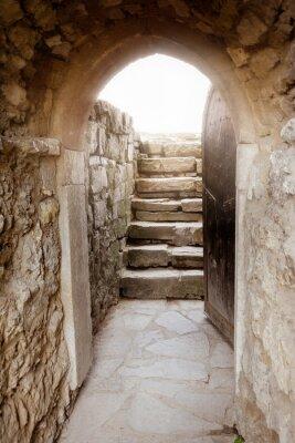 Fototapet Stenmur med öppen dörr och strålar av ljus bakom