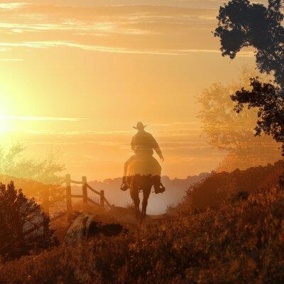 Fototapet Sunset Cowboy. En cowboy rider iväg i solnedgången i transparenta lager av orange och gula moln, ett staket och träd.