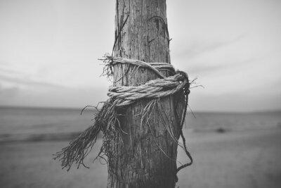 Fototapet Svartvitt slut upp av stolpen på stranden med rep vridna