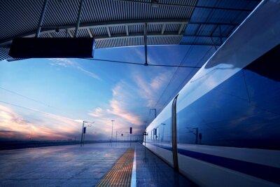 Fototapet tågstopp vid järnvägsstationen med solnedgång