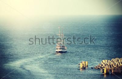 Fototapet Tappning bild av gammalt segelskepp lämnar hamnen.